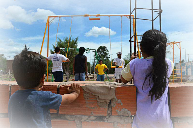 Jóvenes universitarios construyendo una plaza para los niños.